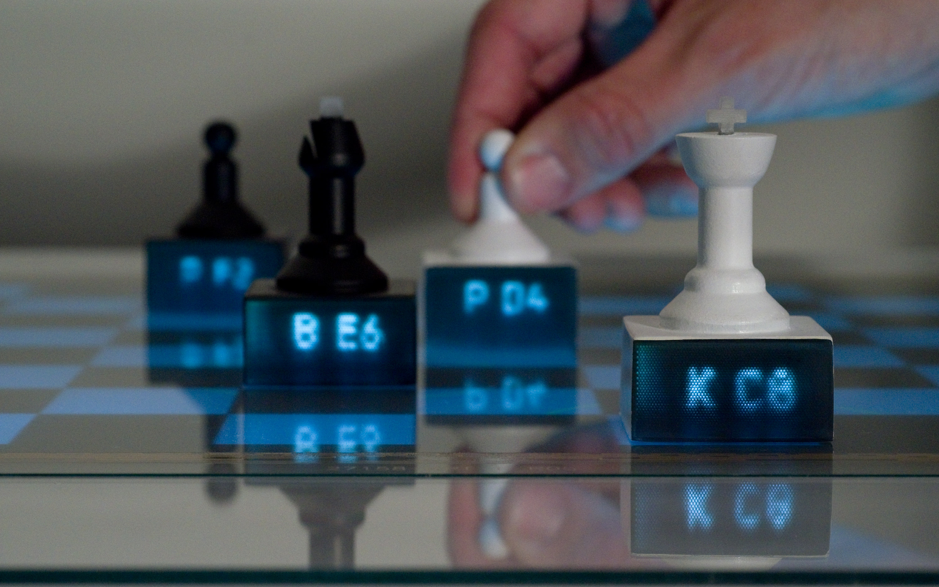 Chess pieces with embedded light pipes display content piped from an